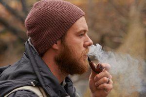 Man Smoking a Pipe Outdoors